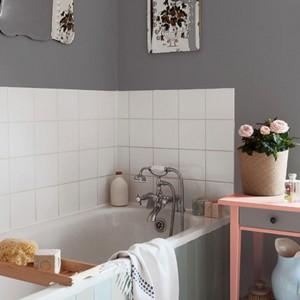 Na ścianie w okolicy wanny i miejsc najbardziej narażonych na działanie wilgoci ułożono białe płytki. Pozostałą część łazienki pomalowano na szary kolor. Na zdjęciu: ściana pomalowana farbą marki Dulux. Fot. Dulux.