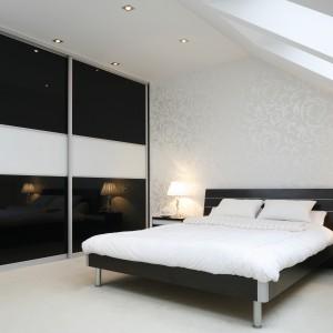 Wnętrze z delikatnym skosem urządzono w czerni i bieli. Eleganckiej aranżacji szyku dodaje delikatnie połyskująca tapeta na ścianie za łóżkiem. Mocnym akcentem jest z kolei duża, pojemna szafa. Projekt: Magdalena Biały. Fot. Bartosz Jarosz.