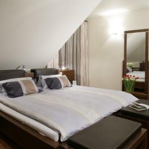 W dużej sypialni miejsce dla łóżka wyznacza ściana ze skosem. To zabieg praktyczny, gdyż pod dużym spadem zmieścić się mogło wyłącznie eleganckie łoże. Projekt: Jacek Radulski. Fot. Monika Filipiuk-Obałek.