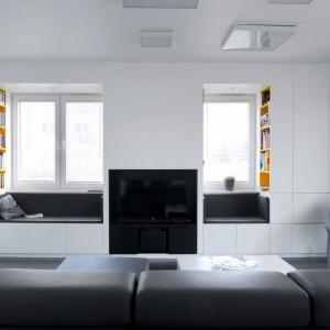 Wnętrze jest pochwałą oszczędnej i uporządkowanej przestrzeni. Zamiast wyodrębnionych regałów czy meblościanek, jest tutaj funkcjonalna i chowająca się w ścianie zabudowa z MDF-u. Projekt i zdjęcia: musk collective design.