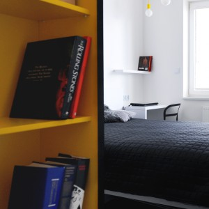 W sypialni nad łóżkiem zawisło delikatnie industrialne oświetlenie. Odsłonięte, edisonowskie żarówki oplatają kolorowe kable, harmonizujące z żywymi kolorami półek na książki. Projekt i zdjęcia: musk collective design.