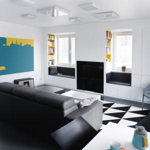 W salonie ożywiającymi elementami są żółte półki we wnękach przy oknach oraz grafika na ścianie. Projekt i zdjęcia: musk collective design.
