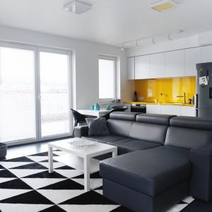 Niewielki stół pełni funkcję jadalni oraz elementu symbolicznie oddzielającego strefę salonu od aneksu kuchennego. Projekt i zdjęcia: musk collective design.