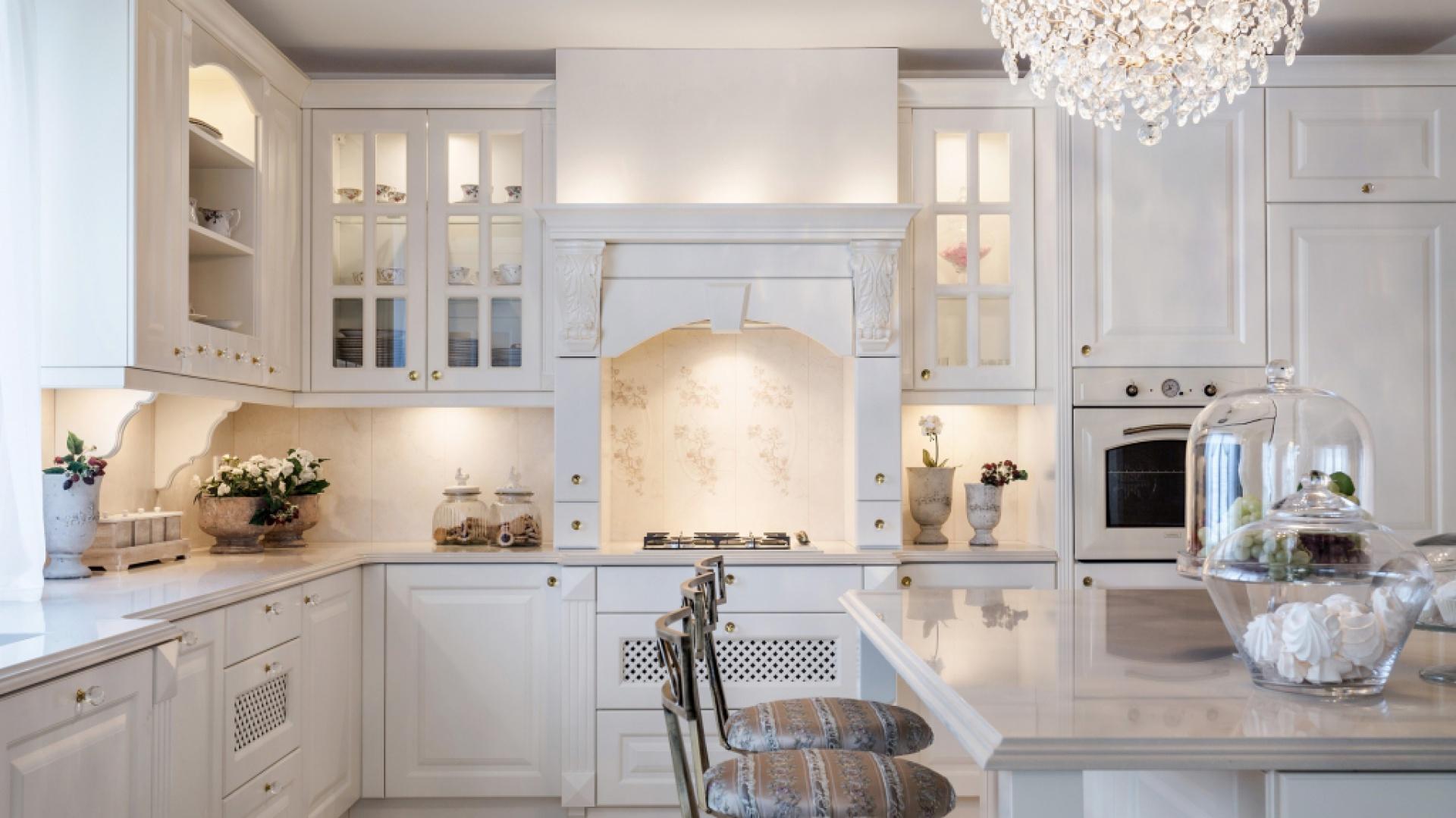 Piękna kuchnia w klasycznym stylu. Górne szafki wykonano w typowym dla tej stylistyki charakterze. Drzwiczki udekorowano przeszkleniami, dodatkowo ozdobionymi szprosami, a całość zdobią dekoracyjne uchwyty. Efektownym i ciekawym rozwiązaniem jest podświetlenie szafek od wewnątrz. Projekt: Małgorzata Błaszczak. Fot. Pracownia Mebli Vigo.