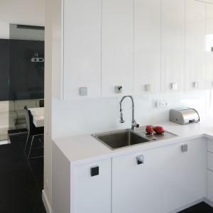 Długie szafki poprowadzone pod sam sufit wydają się jeszcze wyższe poprzez zastosowanie podwójnych drzwiczek. Białą, gładką i połyskującą powierzchnię zdobią duże metalowe uchwyty, przełamujące minimalizm kuchni. Projekt: Dominik Respondek. Fot. Bartosz Jarosz.