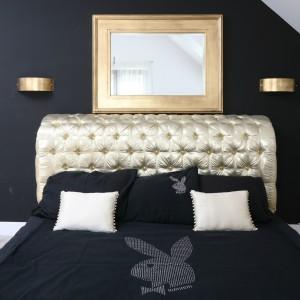 Czarna ściana stanowi idealne tło dla złotego łóżka i dodatków. Charakter aranżacji podkreśla narzuta na łóżko z charakterystycznym króliczkiem. Fot. Bartosz Jarosz.