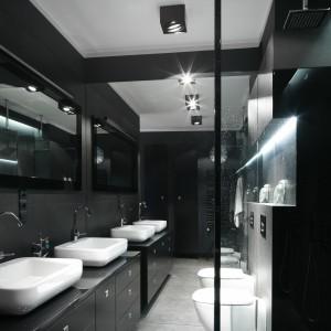 Lustro na całą ścianę optycznie powiększa łazienkę. Wydaje się, że pomieszczenia jest dwa razy większe. Dzięki temu można je było urządzić w przewadze czerni. Projekt: Maciejka Peszyńska-Drews. Fot. Bartosz Jarosz.