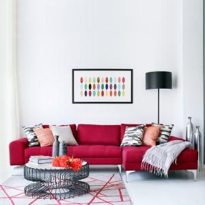 W salonie postawiono na oszczędny, elegancki wystrój, a ton przestrzeni nadają meble i dodatki. Wzrok przyciąga czerwona sofa w stylu retro, grafika z geometrycznym motywem na ścianie i nietuzinkowy stolik kawowy. Projekt: LLI Design. Fot. Zdjęcia: Alex Maguire Photography.