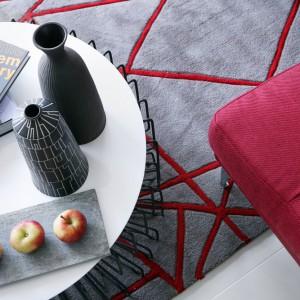 Miękka tapicerka czerwonej sofy i puszysty, satynowy dywan budują przyjemny, przytulny klimat w salonie. Projekt: LLI Design. Fot. Zdjęcia: Alex Maguire Photography.