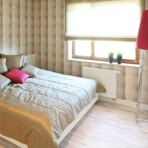 Efektowna tapeta nadaje sypialni miękkości i przytulności. Na kobiecy styl aranżacji jednoznacznie wskazuje lampa podłogowa z abażurem z malinowym kolorze. Projekt: Karolina Łuczyńska. Fot. Bartosz Jarosz.