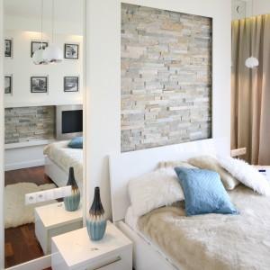Chociaż kamień to materiał surowy i zimny, potrafi nadać aranżacji subtelności. Wykorzystany na ścianie za łóżkiem podkreśla elegancki wygląd nowoczesnej, kobiecej sypialni. Projekt: Małgorzata Mazur. Fot. Bartosz Jarosz.
