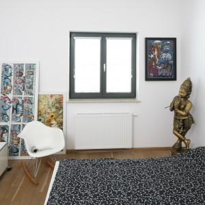 Dzięki temu, że okno w ciemnej ramie pozostawiono bez żadnej dekoracji, komponuje się ono z obrazami wiszącymi na ścianach. Fot. Bartosz Jarosz.