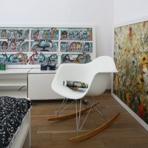 Kolorowe grafiki znalazły miejsce nie tylko na ścianach. Dwie z nich poustawiano nonszalancko na podłodze i szafce, dzięki czemu wnętrze zyskało kokieteryjny wygląd. Fot. Bartosz Jarosz.