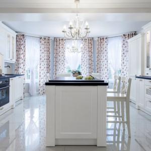 Elegancka klasyczna kuchnia ze zdobionymi frontami w kolorze złamanej bieli i ciemnobrązowym, czekoladowym blatem. Całości dopełniają ażurowe wstawki i delikatne przeszklenia. Fot. Pracownia Mebli Vigo, kuchnia Rose.