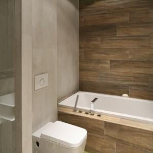 Połączenie szarości, bieli oraz płytek o fakturze drewna nadało niewielkiej łazience nowoczesny, ale i elegancki klimat. Projekt: Dominik Respondek. Fot. Bartosz Jarosz.