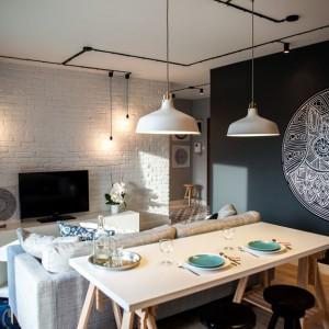 W niedużym salonie ścianę z telewizorem zdobi biała cegła, która kontrastuje z tą pomalowaną na czarno. Projekt: Michał i Marta Raca. Fot. Adam Ościłowski.