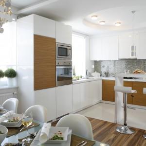 Drewno i bieli to duet idealny, który w kuchni sprawdza się znakomicie. Sprawia, że przestrzeń jest jasna, rozświetlona, a jednocześnie bardziej ciepła. Projekt: Małgorzata Mazur. Fot. Bartosz Jarosz.