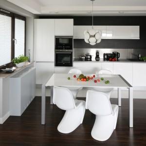 W urządzonym w minimalistycznym duchu niedużym apartamencie dominuje biel, której monochromatyczność przerywa czerń, będąca mocnym akcentem stylistycznym w otwartej strefie dziennej. Projekt: Agnieszka Burzykowska-Walkosz. Fot. Bartosz Jarosz.