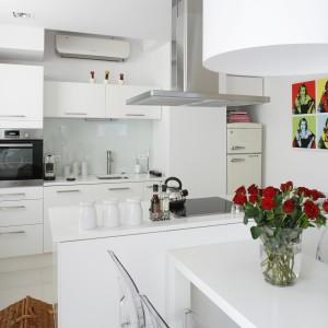 Biel całkowicie zdominowała kuchnię otwartą na salon i połączoną z jadalnią. W tym kolorze są blaty, meble, podłoga oraz stół w jadalni. Nic nie zakłóca jasnej przestrzeni.Projekt: Piotr Gierałtowski. Fot. Bartosz Jarosz.