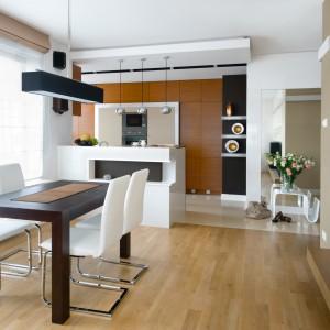 Przewaga drewna w tej kuchni w dość ciemnym wybarwieniu wcale nie sprawiła, że wnętrze jest ciemne. Biel, jak zawsze zrobiła swoje i pięknie rozjaśniła przestrzeń. Projekt: Monika Kosakowska. Fot. Monika Kosakowska.