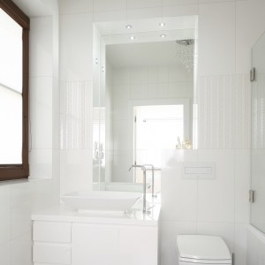 Zaledwie 2,5-metrowa łazienka urządzona jest w bieli. Połyskujące powierzchnie odbijają światło i optycznie powiększają wnętrze. Projekt: Kamila Paszkiewicz. Fot. Bartosz Jarosz.