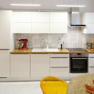 Długie, płaskie, wiszące lampy są nowoczesnym akcentem w kuchni, korespondującym z prostą formą frontów. Projekt: Agnieszka Żyła. Fot. Bartosz Jarosz.