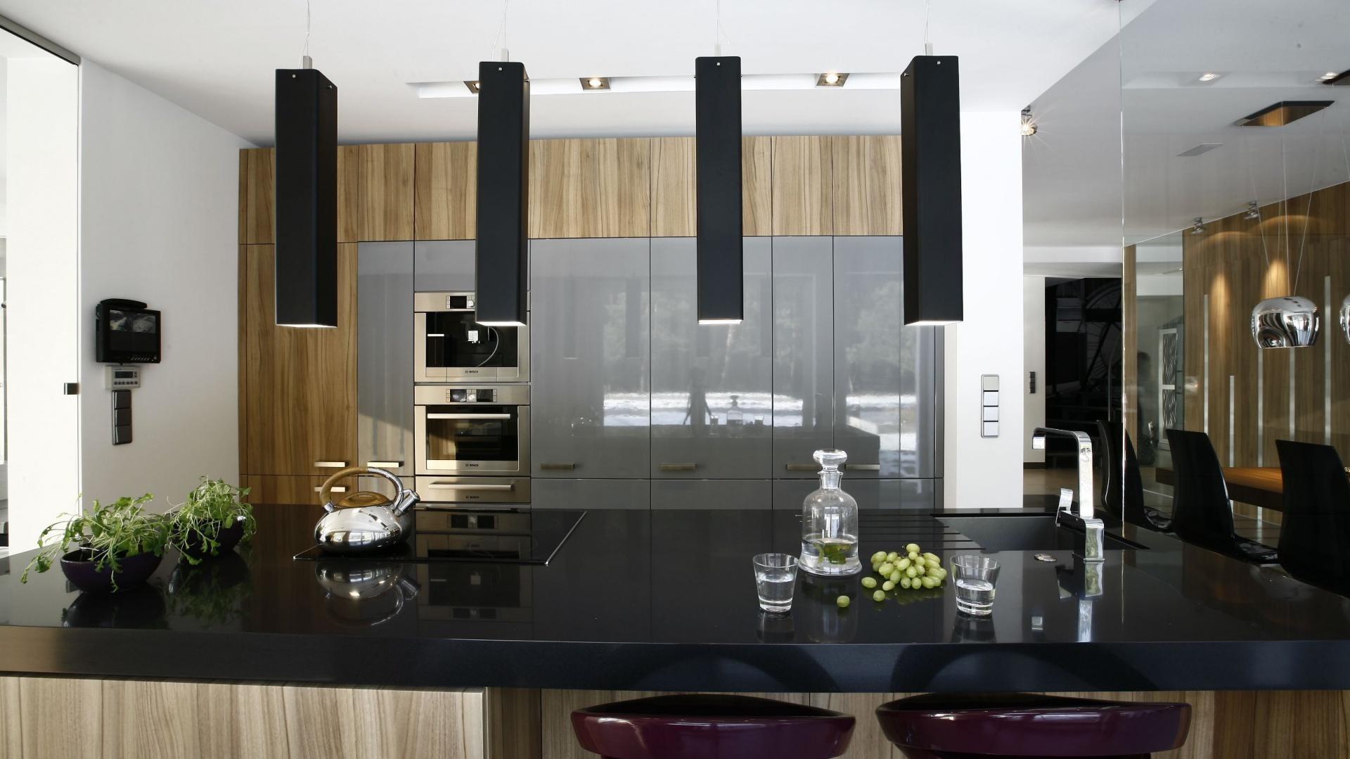 W tej nowoczesnej kuchni cała powierzchnia robocza została przeniesiona na dużą wyspę. Odpowiednie oświetlenie blatu zapewniają cztery dekoracyjne lampy w długich, prostokątnych aluminiowych abażurach w ciemnym kolorze, harmonizujący z barwą blatu. Projekt: Liliana Masewicz-Kowalska. Fot. Marcin Onufryjuk.