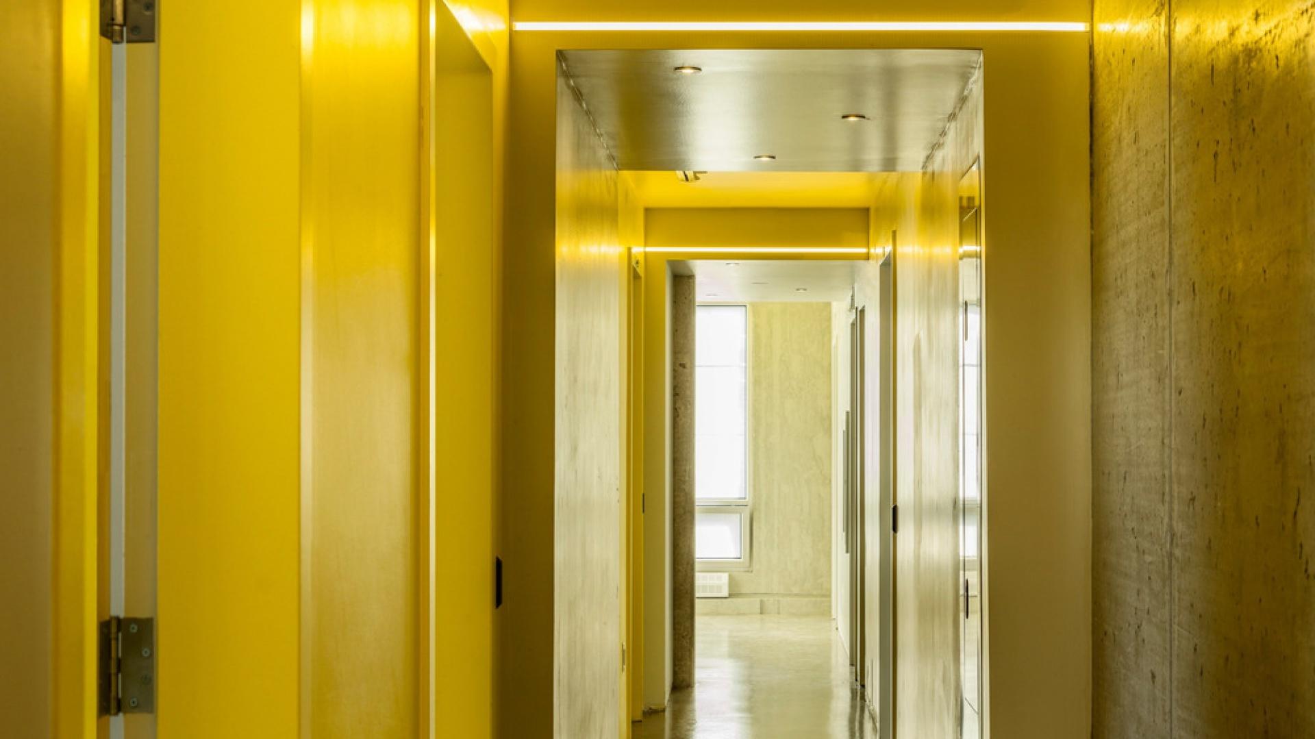 W przestrzeni korytarza dominuje mocny kolor - kanarkowa żółć, która przebija dominację szarości. Projekt: KANVA. Fot. Marc Cramer.