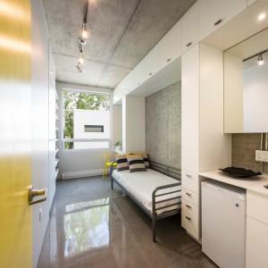 Poszczególne pokoje studentów zostały urządzone w oparciu o aspekt funkcjonalny oraz z troską o uporządkowanie przestrzeni. Łóżko wpasowano we wnękę, otoczoną praktyczną zabudową. Projekt: KANVA. Fot. Marc Cramer.