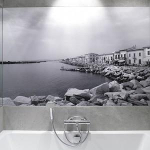 Ogromne lustro umieszczone na ścianie optycznie powiększa wnętrze łazienki.Dodatkowo obija się w nim fototapeta, co zapewnia ciekawy efekt estetyczny. Projekt: Lucyna Kołodziejska. Fot. Bartosz Jarosz.