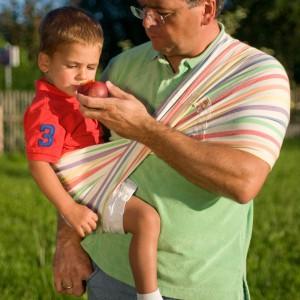 Trzymanie dziecka przy pomocy chusty daję rękom większą swobodę, dzięki czemu można np. jednocześnie trzymać i karmić malucha. Fot. Babytuch.