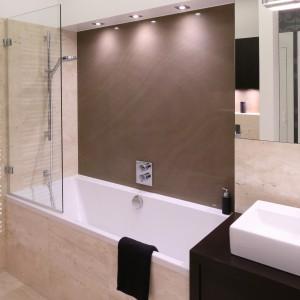 W tej łazience można wziąć długą kąpieli lub szybki prysznic. Wanna, dzięki zastosowaniu szklanego parawanu doskonale spełnia również rolę kabiny prysznicowej. Projekt: Katarzyna Mikulska-Sękalska. Fot. Bartosz Jarosz.