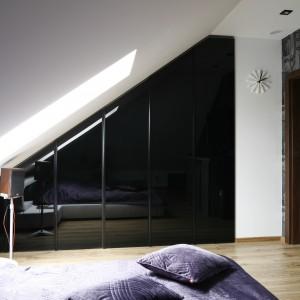 We wnętrzu ograniczonym skosami rolę tradycyjnej szafy pełni praktyczna zabudowa pod skosem. Czarne fronty z lakierowanego MDF-u skrywają garderobę gospodarzy, podkreślając nowoczesny styl sypialni. Projekt: Marta Kilan. Fot. Bartosz Jarosz.