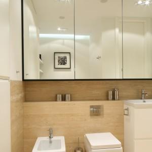 Nad zabudową umieszczono pojemne szafki, które ukryto za lustrzanymi frontami. Dzięki temu łazienka wydaje się optycznie większa. Projekt: Anna Maria Sokołowska. Fot. Bartosz Jarosz.