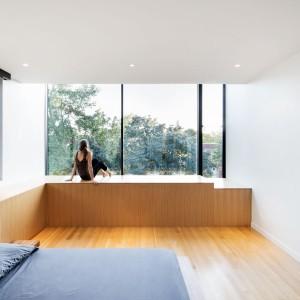 Sypialnię małżeńską usytuowano w miejscu odseparowanym od części domu z pokojami dzieci, zapewniając intymność pani i panu domu. Ściana z panoramicznym przeszkleniem, odsłaniająca widok na uspokajającą zieleń dodatkowo zachęca do relaksu. Projekt: Nature Humaine. Fot. Adrien Williams.