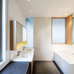 Podłogę i ściany w łazience wykończono drobniutką mozaiką, która zlewa się w jednorodne powierzchnie w czarnym i białym kolorze. Cieplejszym akcentem są drewniane elementy. Projekt: Nature Humaine. Fot. Adrien Williams.