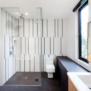 Na wskroś nowoczesna łazienka. Bezprogowa strefa prysznica zamknięta została w proste, delikatne przeszklenia. Wc przybrało ostre kąty i futurystyczny kształt, z którym harmonizuje płytka, prostokątna umywalka i pionowe wzory na ścianie za prysznicem i sanitariatem.  Projekt: Nature Humaine. Fot. Adrien Williams.
