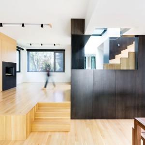 Powierzchnia parteru ma dwa poziomy - niższą część z jadalnią i salonem otwartym na dwie kondygnacje oraz usytuowaną na swoistym podeście część, sąsiadującą z przedsionkiem. Tutaj znajduje się drugi, mniejszy pokój dzienny oraz wejście do klatki schodowej. Projekt: Nature Humaine. Fot. Adrien Williams.