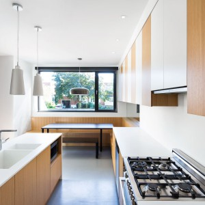 W kuchni znalazło się miejsce na wpasowanie niewielkiej przestrzeni jadalnianej. Tutaj domownicy mogą zjeść szybkie śniadanie - podczas, gdy sąsiadująca z kuchnią jadalnia może posłużyć za miejsce na większe, rodzinne obiady. Projekt: Nature Humaine. Fot. Adrien Williams.