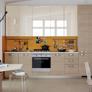 Drewno i jego dekory można łączyć z najróżniejszymi materiałami, kolorami i teksturami. Gładkie, beżowe fronty w wysokim połysku idealnie harmonizują z drzwiczkami w kolorze drewna. Fot. Scavolini, kuchnia z kolekcji Feel.