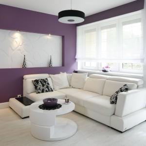 Salon z aneksem kuchennym urządzono w czystej bieli. Jedynym dodatkiem kolorystycznym jest tu wykonana z płyty gipsowo-kartonowej ścianka za kanapą, którą pomalowano na fioletowo. Projekt: Joanna Ochota. Fot. Bartosz Jarosz.