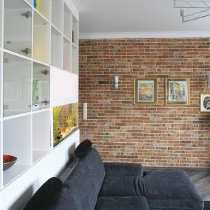 Stara, stuletnia cegła, pochodząca z rozbiórki, zdobi główna ścianę w salonie. Projekt: Agnieszka Ludwinowska. Fot. Bartosz Jarosz.
