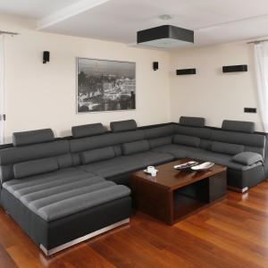 Centrum wypoczynku organizuje duża, narożna kanapa o nietypowym poszyciu tapicerki. Jej szaro-czarny kolor stanowi istotny element dekoracyjny wnętrza. Projekt: Marta Kilan. Fot. Bartosz Jarosz.