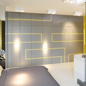 Szara ściana z żółtym geometrycznym wzorem skrywa pojemną szafę i jednocześnie spaja wizualnie przestrzeń sypialni i łazienki, już i tak mocno ze sobą scalonych. Projekt: Monika i Adam Bronikowscy. Fot. Bartosz Jarosz.