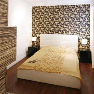 Chociaż sypialnia jest niewielka, to jednak bardzo elegancka. Dekoracje ścienne w kolorze brązu i waniliowego kremu dodają wnętrzu szyku, efektownie je ocieplając. Tekstylne dekoracje czynią natomiast sypialnię bardziej subtelną. Projekt: Piotr Stanisz. Fot. Bartosz Jarosz.