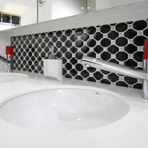 Czerwone elementy baterii łazienkowych efektownie wyróżniają się na tle czarnych, dekoracyjnych płytek. Projekt: Marta Kilan. Fot. Bartosz Jarosz.