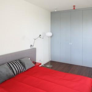 Krótszą ścianę pomieszczenia w całości wykorzystano pod praktyczną zabudowę. Jasnoszare fronty korespondują z tapicerowanym zagłówkiem łóżka, podkreślając zarazem minimalistyczny styl wnętrza. Projekt: Iza Szewc. Fot. Bartosz Jarosz.