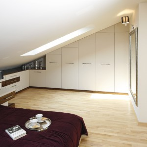 Ścianę o dużym spadzie w całości zabudowano szafkami w kolorze ciepłej bieli. Przy ścianie ze skosem przechodzi ona w niską, elegancką komodę, sięgającą łóżka. Projekt: Jolanta Kwilman. Fot. Bartosz Jarosz.