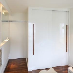 W długim i dość wąskim pomieszczeniu garderobę urządzono przy drzwiach. Tuż obok, na całej długości ściany zawieszono lustro, które dodaje przestronności i optycznie powiększa wnętrze. Projekt: Małgorzata Mazur. Fot. Bartosz Jarosz.
