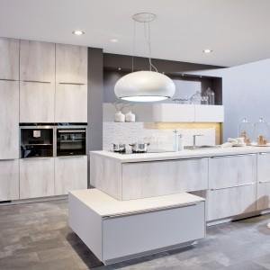Jasne, nowoczesne meble kuchenne z pionowym rysunkiem drewna tworzą ciekawą kompozycją z szarymi ścianami i podłogą. Oryginalnie prezentująca się wyspa składa się z dwóch części - większej w kolorze drewna i mniejszej - białej. Fot. Brigitte Kuechen.